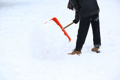 Man with snow shovel cleans sidewalks Royalty Free Stock Photos