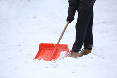 Man with snow shovel cleans sidewalks Royalty Free Stock Photography