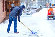 Man with snow shovel cleans sidewalks in winter during snowfall. Winter time in Europe. Young man in warm winter clothes stock photos