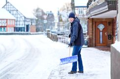 Man with snow shovel cleans sidewalks in winter during snowfall. Winter time in Europe. Young man in warm winter clothes stock image