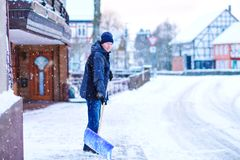 Man with snow shovel cleans sidewalks in winter during snowfall. Winter time in Europe. Young man in warm winter clothes royalty free stock photos