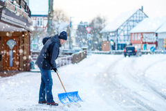 Man with snow shovel cleans sidewalks in winter Stock Image
