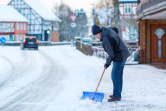 Man with snow shovel cleans sidewalks in winter Royalty Free Stock Photography