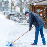 Man with snow shovel cleans sidewalks in winter Stock Images