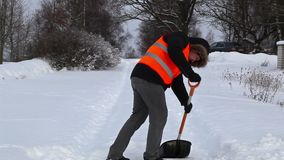 Man with snow shovel on the snovy road in winter stock video