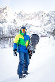 The man with the snowboard. Is on the background of mountains stock photo