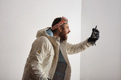 Man in snowboard gear screaming into walkie talkie royalty free stock photography