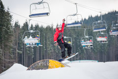 Man on the snowboard jumping over a hurdle. In winter day with ski lifts in background at a winter resort Royalty Free Stock Photo