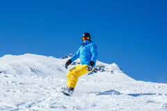 Man on snowboard. Moving down the hill royalty free stock image