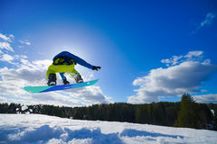 Man on the snowboard. Young man on the snowboard jumping over the slope in winter stock image