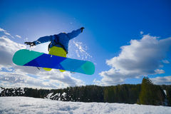 Man on the snowboard. Young man on the snowboard jumping over the slope in winter royalty free stock photography