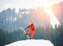 Man snowboarder jumping on the top of the snowy hill with snowboard in the evening at sunset. Ski slope, forests and mountains on the background. Skiing and Stock Photo