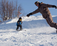 Man snowboarder and little skier. Snowboarder and boy skier on the slope Royalty Free Stock Photos