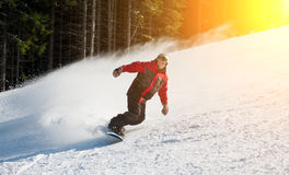 Man snowboarder slides down from the mountain in winter day. Overlooking the snowy slope at a winter resort Royalty Free Stock Photos