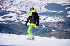 Man snowboarder  on a slope in the winter mountain Royalty Free Stock Photo