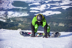 Man snowboarder  on a slope in the winter mountain Stock Images