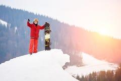 Man snowboarderanseendet på överkanten av den snöig lutningen med snowboarden, visningtummar upp på vintern skidar semesterorten Arkivbild