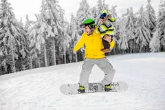Man snowboarding at the mountains. Man in colorful sports clothes riding the snowboard on the snowy mountains with beautiful trees on the background stock photography