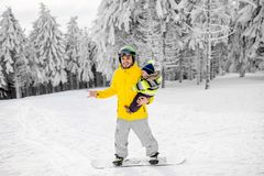 Man snowboarding at the mountains. Man in colorful sports clothes riding the snowboard on the snowy mountains with beautiful trees on the background royalty free stock photos