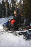 Man on snowmobile. Young man sitting on snowmobile in snow with helmet on lap smiling Royalty Free Stock Image