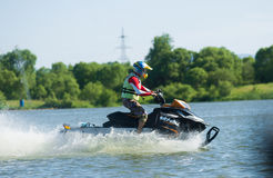 Man on snowmobile goes fast on the water in summer Royalty Free Stock Images
