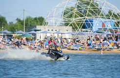 Man on snowmobile goes fast on the water in summer Royalty Free Stock Image