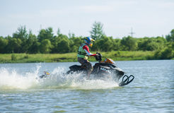 Man on snowmobile goes fast on the water in summer Stock Photography