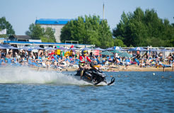 Man on snowmobile goes fast on the water in summer Stock Photo