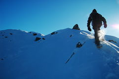 Man Snowshoeing. A man snowshoeing along a ridge in deep snow Royalty Free Stock Image