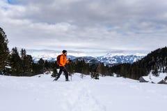 Man snowshoeing on Scheibelalm in Hohentauern view to Ennstaler Alps. Man in orange jacket snowshoeing on Scheibelalm in holiday resort Hohentauern with royalty free stock images