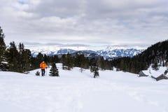 Man snowshoeing on Scheibelalm in Hohentauern view to Ennstaler Alps. Man in orange jacket snowshoeing on Scheibelalm in holiday resort Hohentauern with royalty free stock image