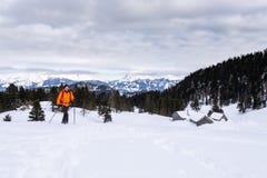 Man snowshoeing on Scheibelalm in Hohentauern view to Ennstaler Alps. Man in orange jacket snowshoeing on Scheibelalm in holiday resort Hohentauern with stock images