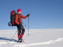 The man in snowshoes in the mountains indicates the direction. Royalty Free Stock Images
