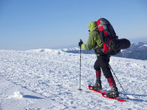 The man in snowshoes in the mountains. Royalty Free Stock Photo
