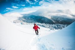 A man in snowshoes in the mountains. stock photography