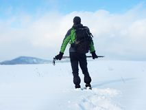 Man with snowshoes take a rest in snow. Hiker snowshoeing. Man with snowshoes and backpack take a rest in snow. Hiker in winter jacket and trekking trousers Stock Image