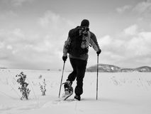 Man with snowshoes take a rest in snow. Hiker snowshoeing Royalty Free Stock Photo