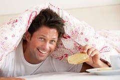 Man Snuggled Under Duvet Eating Breakfast. Smiling Holdind Toast Royalty Free Stock Photos
