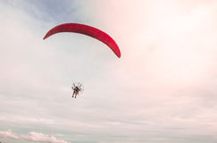 A man soaring into the sky with paramotor extreme sport adventure in summer day time with a clear sky background. Stock Photo