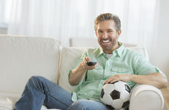 Man With Soccer Ball Watching TV. Smiling mature man with soccer ball watching TV on sofa Stock Photos