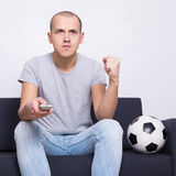 Man soccer fan sitting on sofa with ball and watching tv at home Stock Images