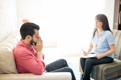 Man with social anxiety at psychotherapist for treatment. Man suffering from social anxiety visiting psychotherapist for treatment and solutions Royalty Free Stock Images