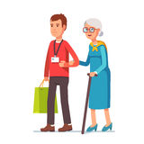 Man social worker helping elder grey haired woman. Young man social worker helping elder grey haired woman with grocery shopping. Strolling with old lady. Flat Stock Image