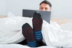 Man with socks in his leg using a laptop Stock Photo