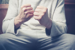 Man on sofa with clenched fists Royalty Free Stock Images