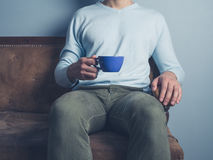 Man on sofa drinking coffee Royalty Free Stock Images