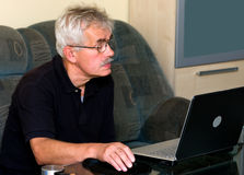 Man on sofa with laptop Stock Image