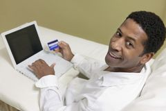 Man on sofa with laptop and credit card Royalty Free Stock Photography
