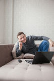 The man on a sofa with laptop Royalty Free Stock Image