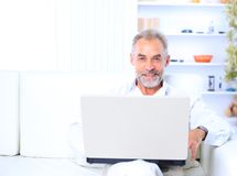 Man in sofa with laptop Royalty Free Stock Photography